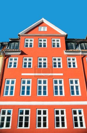 low angle view of beautiful traditional red house with white windows at sunny day, copenhagen