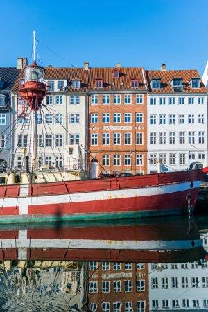 COPENHAGEN, DENMARK - 06 MAY, 2018: boat and houses reflected in water at Nyhavn pier, copenhagen, denmark