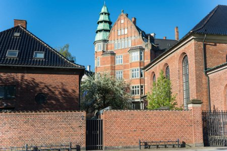 brick wall, church and houses at sunny day in copenhagen, denmark