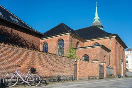 Photo pour Vélo garé près de mur de briques et belle église contre le ciel bleu, Copenhague, Danemark - image libre de droit