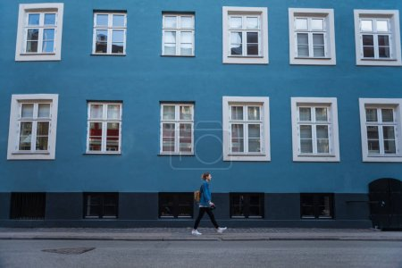 side view of young woman walking near blue house with large windows in copenhagen, denmark