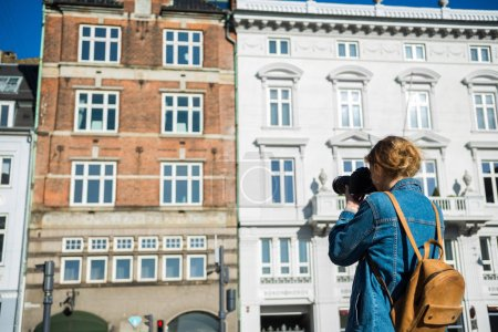 Photo for Back view of girl with camera photographing beautiful houses in copenhagen, denmark - Royalty Free Image