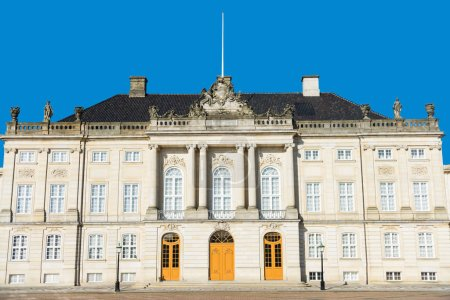 beautiful architecture of historical Amalienborg castle with columns and statues in copenhagen, denmark