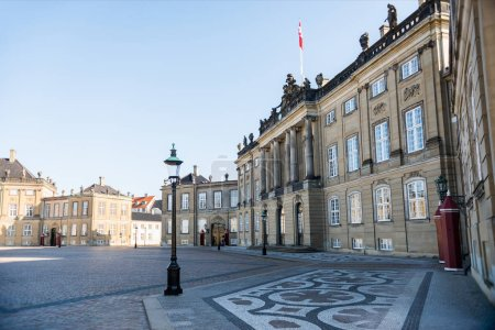 empty Amalienborg Square with historical buildings, pavement and street lamps in copenhagen, denmark