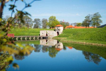 gates to famous Kastellet or Citadel reflected in calm water, copenhagen, denmark