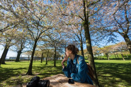 Photo for Young woman smoking cigarette while sitting at wooden table with camera and smartphone in beautiful park with blossoming trees, copenhagen, denmark - Royalty Free Image