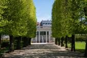 """Постер, картина, фотообои """"красивая аллея с зелеными деревьями и историческое здание с колоннами и статуями в Копенгагене, Дания"""""""
