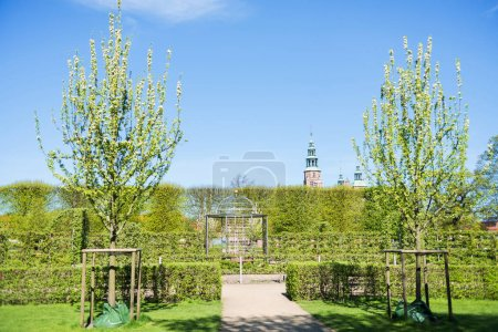 beautiful park with blossoming trees and green bushes and Rosenborg castle in Copenhagen, Denmark