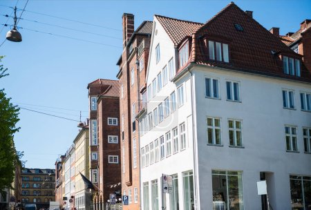 low angle view of beautiful houses and street at sunny day in copenhagen, denmark