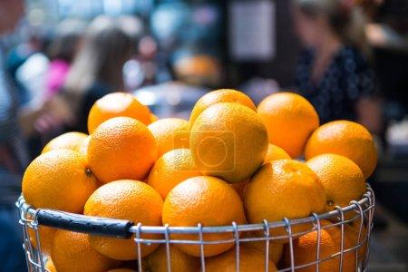 Photo pour Foyer sélectif de pile d'oranges dans le panier en métal sur fond flou - image libre de droit