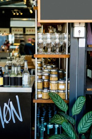 selective focus of shelves with jars with cereals, glasses and bottles in cafe