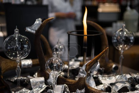 Photo for Selective focus of fire, flasks and foil on table and female scientist on blurred background - Royalty Free Image