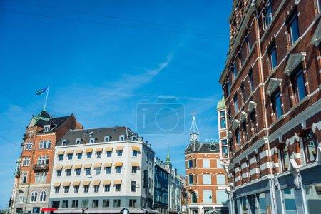 cityscape with buildings under bright blue sky in Copenhagen, Denmark