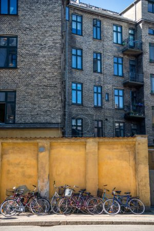 building and parked bicycles near yellow stone wall in Copenhagen, Denmark