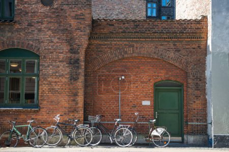 parked bicycles near brick wall of building of Copenhagen, Denmark