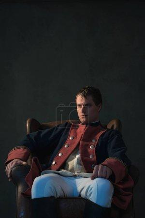 Photo pour Homme de style empire, assis sur chaise. - image libre de droit