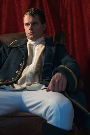 Serious historical regency man sits in front of red curtain.