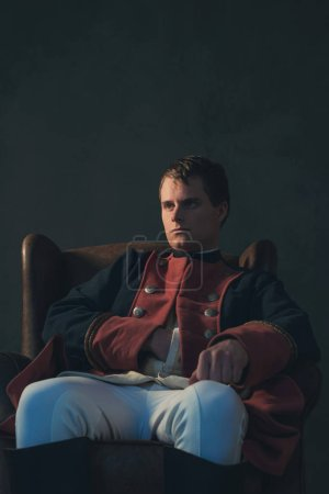 Photo for Historical regency man with hand in jacket sitting in chair. - Royalty Free Image