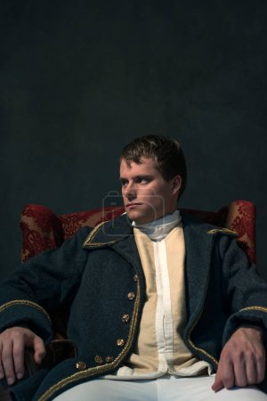 Photo for Historical biedermeier man sits in red chair. - Royalty Free Image