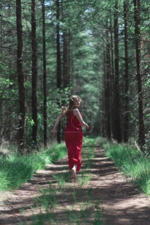 Blonde woman in red dress running away from camera on forest path.