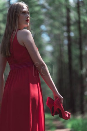 Blonde woman in red dress holding shoes in hand looking over shoulder.
