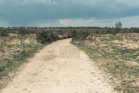 Photo for Dirt road in hilly landscape under cloudy sky. - Royalty Free Image
