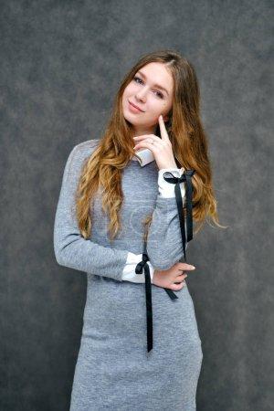 Photo pour Portrait de concept d'un manager d'une fille heureuse brunet avec de beaux longs cheveux agréable. Elle se tient debout dans une robe grise souriant sur fond gris en pleine croissance. - image libre de droit