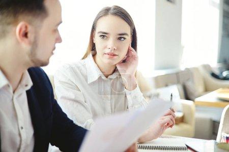 Planifier la stratégie à la réunion des partenaires commerciaux. Femme d'affaires posant des questions à collègue masculin munies de documents de