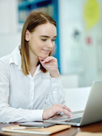 Side view of attractive young female putting chin on hand searching information on laptop and smiling in library