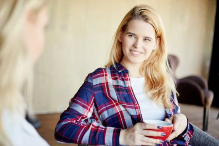 Beautiful young blonde woman in checkered shirt holding cup of coffee and smiling to unrecognizable female friend