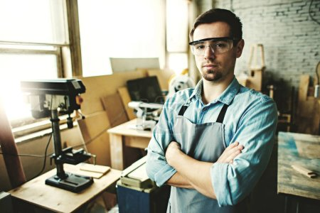 Portrait of confident young carpenter wearing apron and protective eyeglasses posing cross-armed in his woodworking sho