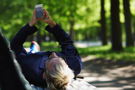 Blond male in glasses and checkered jacket lying on back on white park bench and looking at mobile phone in stretched out arms on sunny summer day on blurred background