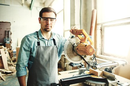 Young woodworker wearing apron and protective eyeglasses posing with circular electric saw in his worksho