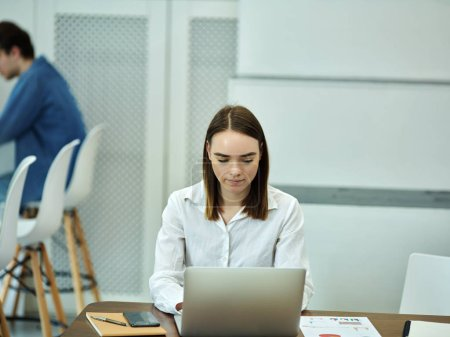 Young concentrated pretty student sitting at table preparing study tasks typing on laptop in library