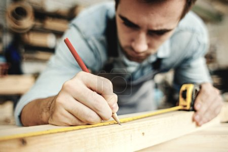 Concentrated professional carpenter measuring wood plank and making mark with penci