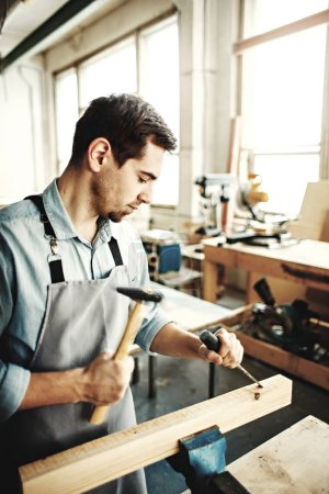 Portrait of concentrated carpenter working with timber in his workshop; woodworker using hammer and chisel to make hole in wooden plank
