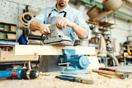 Hands of skillful young carpenter sanding wood plank placed in workbench vice