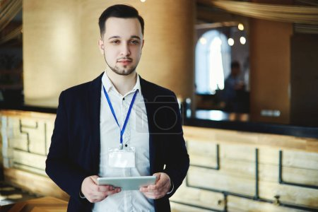 Portrait of young businessman wearing blank badge posing at business event with tablet in his hands