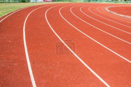 Photo pour Plancher couvert rouge du stade de course avec des lignes de route - image libre de droit