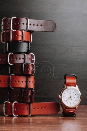 Photo pour Ceintures en cuir sur table en bois avec montre-bracelet - image libre de droit