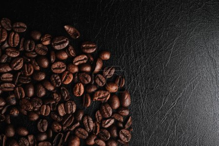 Photo for Partial view of brown coffee beans, coffee background on black leather surface - Royalty Free Image