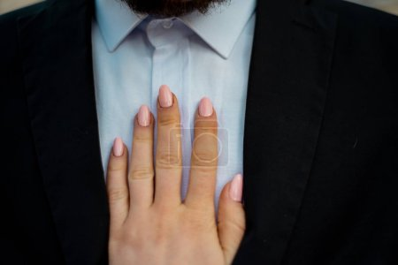 Photo for Cropped image of female hand touching male chest in shirt - Royalty Free Image
