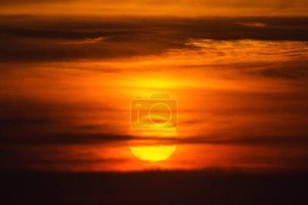 Photo pour Soleil au coucher du soleil à l'arrière des nuages rouges - image libre de droit