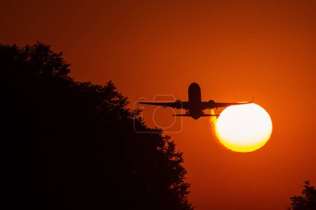 Photo for Silhouette of an air plane over the sun with beautiful red clouds in background - Royalty Free Image