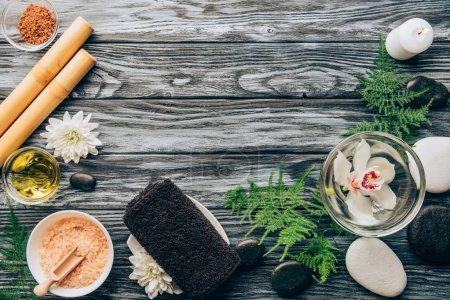 Photo pour Vue de dessus des cailloux disposés, sel, huile, bâtons de bambou et fleur d'orchidée dans un bol pour spa et massage sur fond en bois - image libre de droit