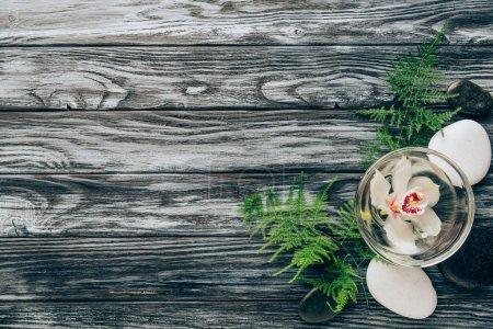 Photo pour Vue de dessus des cailloux disposés, Fougère et fleur d'orchidée dans un bol pour spa et massage sur fond en bois - image libre de droit