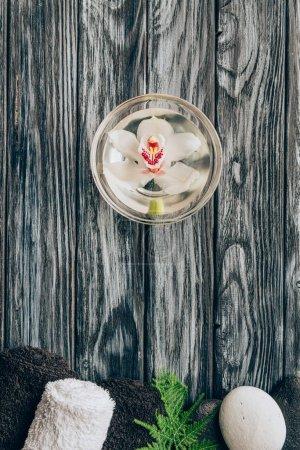 Photo pour Vue de dessus de la fleur d'orchidée disposée dans le bol, des serviettes et des cailloux pour spa et massage sur table en bois - image libre de droit