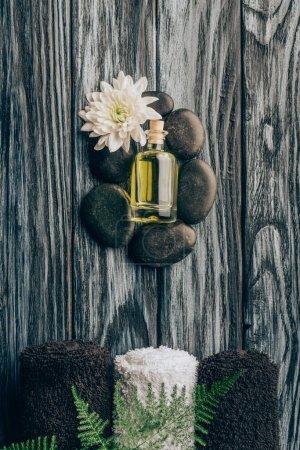 Photo pour Vue de dessus des cailloux disposés huile essentielle noir avec la fleur de chrysanthème et de serviettes pour massage et spa sur une surface en bois - image libre de droit