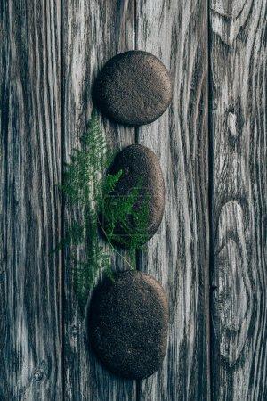 Photo pour Vue de dessus de fougère arrangé et cailloux noirs pour massage et spa sur fond en bois - image libre de droit