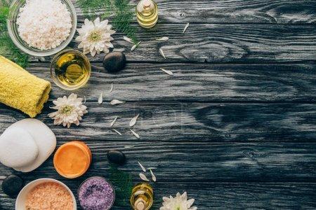 Photo pour Plat Posez avec spa et massage arrangement de traitement avec huiles essentielles, sel, serviette et galets sur le dessus de table en bois - image libre de droit